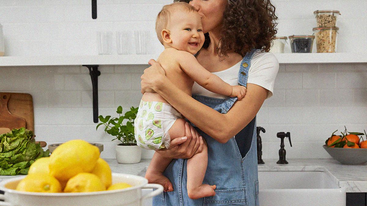 Mutter hält ihr Kind in den Armen und küsst es