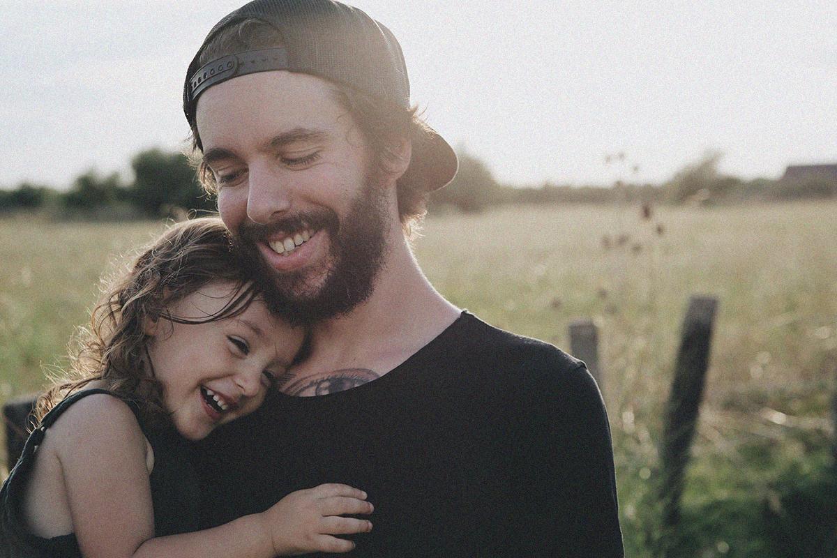 Junger Vater hält sein Kind in den Armen