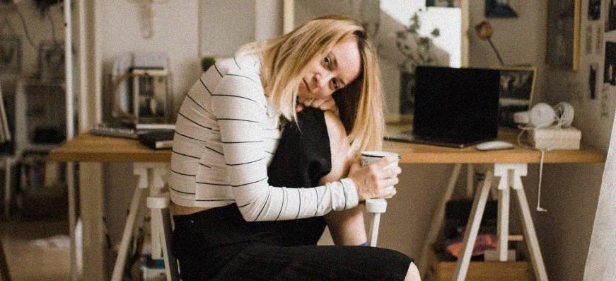 Une jeune femme assise tien un verre