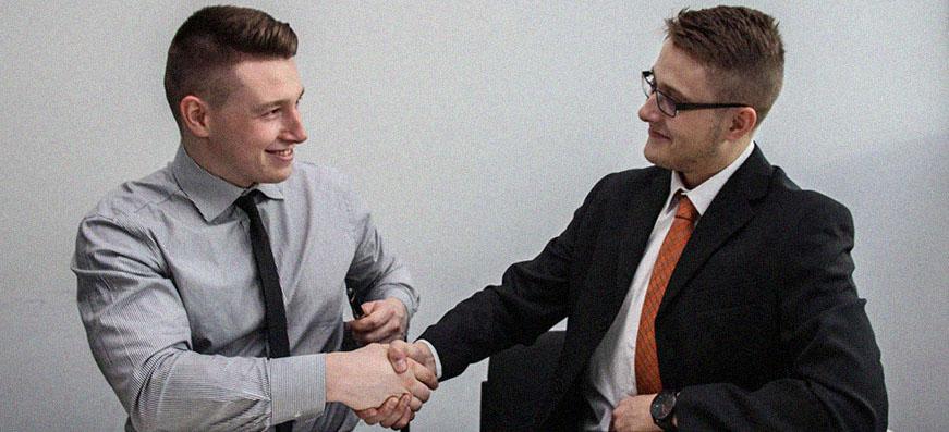 deux hommes en entretien d'embauche se serrent la main et sourient