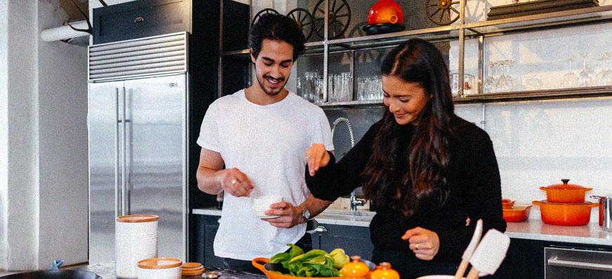 tjej och kille lagar mat