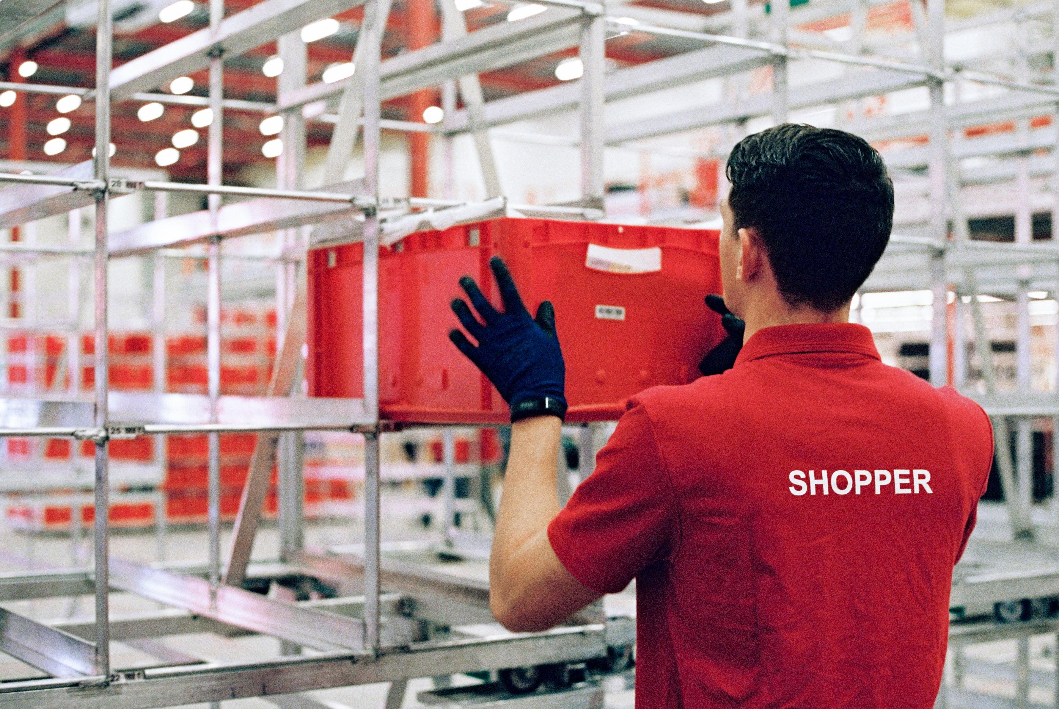 """Ein Mann in rotem Picnic T-Shirt mit der Aufschrift """"Shopper"""" räumt eine rote Kiste ins Regal ein."""