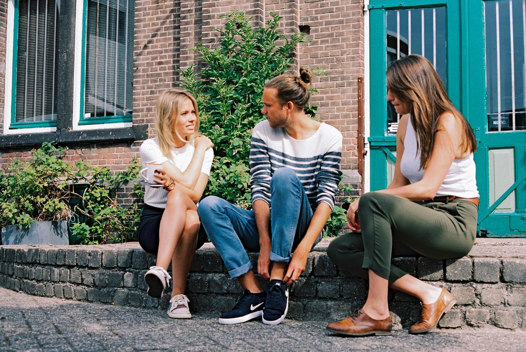 Zwei Frauen sitzen neben einem Mann draußen auf einer kleinen Mauer.
