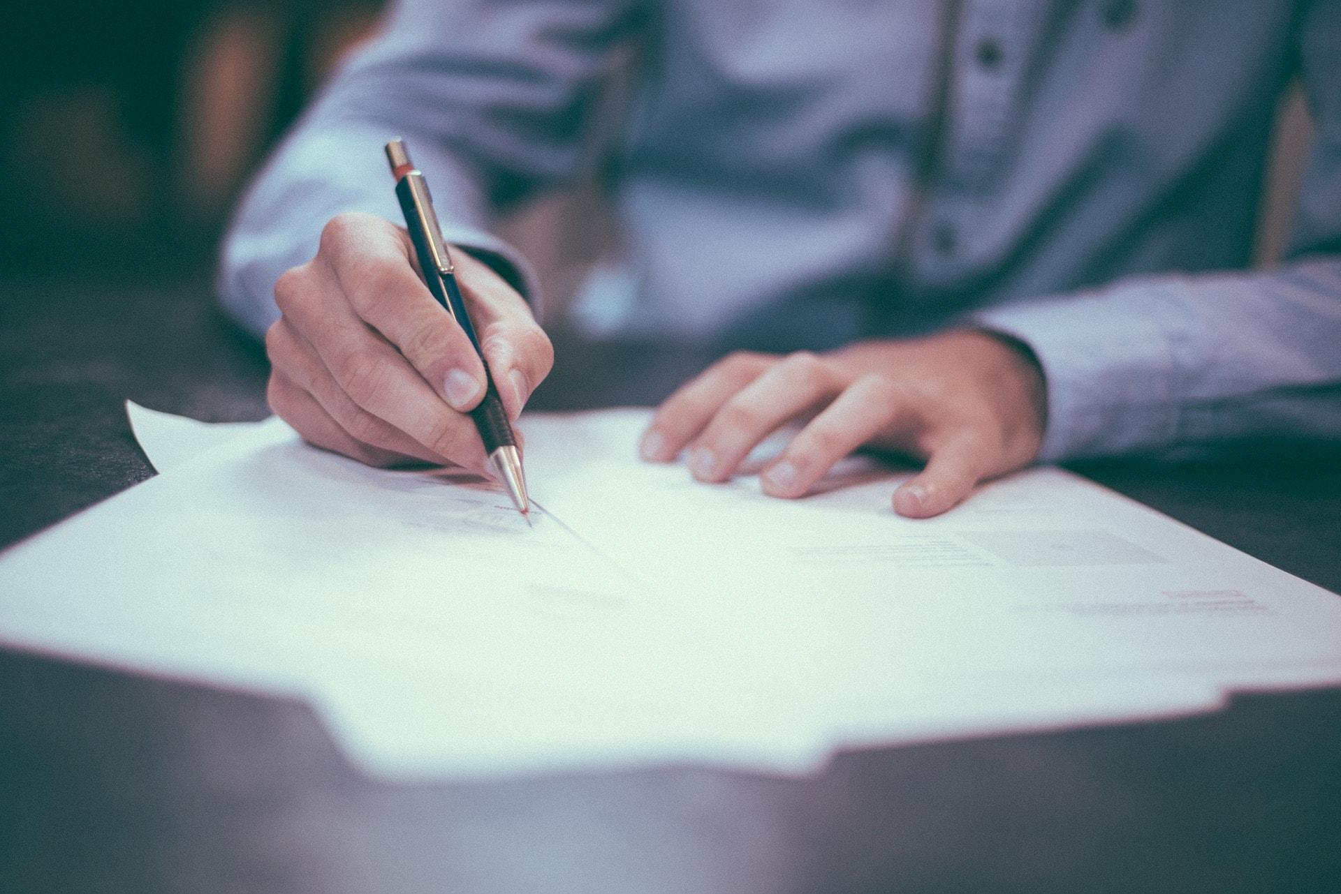 Ein Mann in einem hellblauen Hemd unterschreibt ein Blatt Papier mit einem Kugelschreiber.