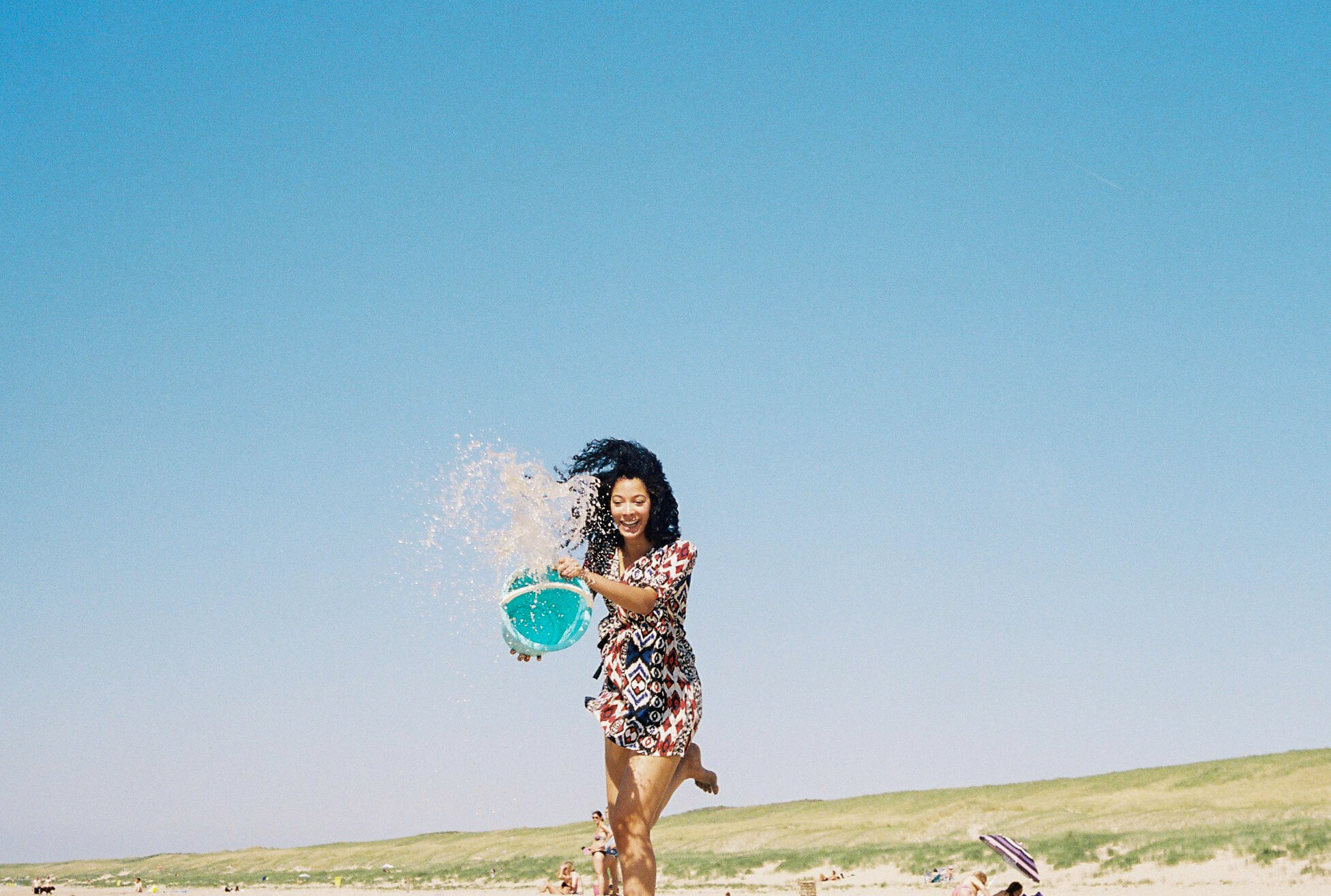 Chica joven con cubo de agua en la playa
