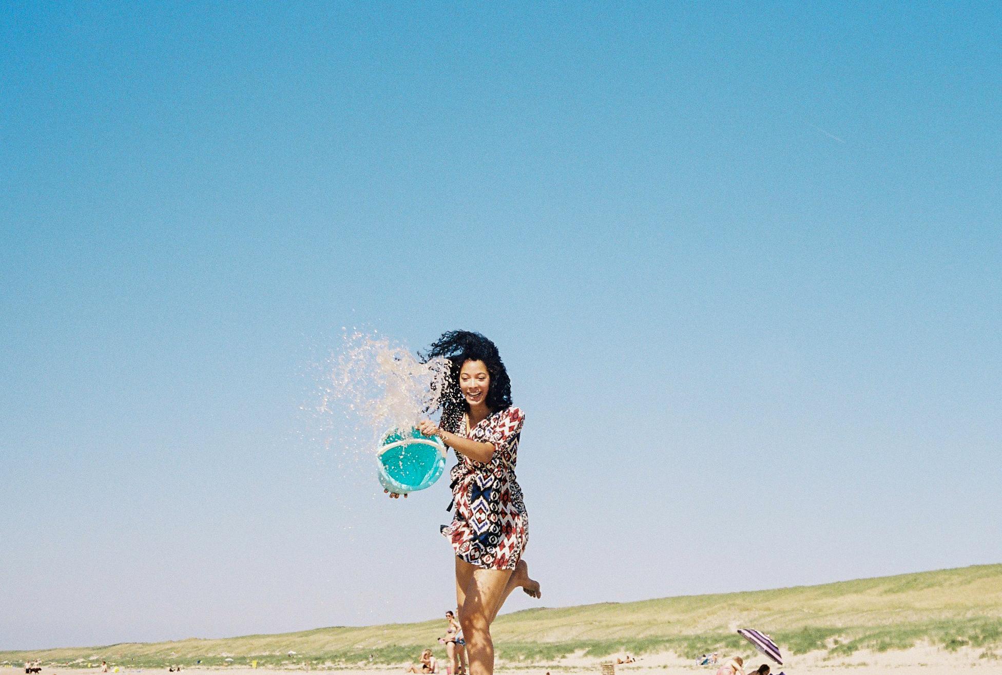 Girl throwing bucket of water