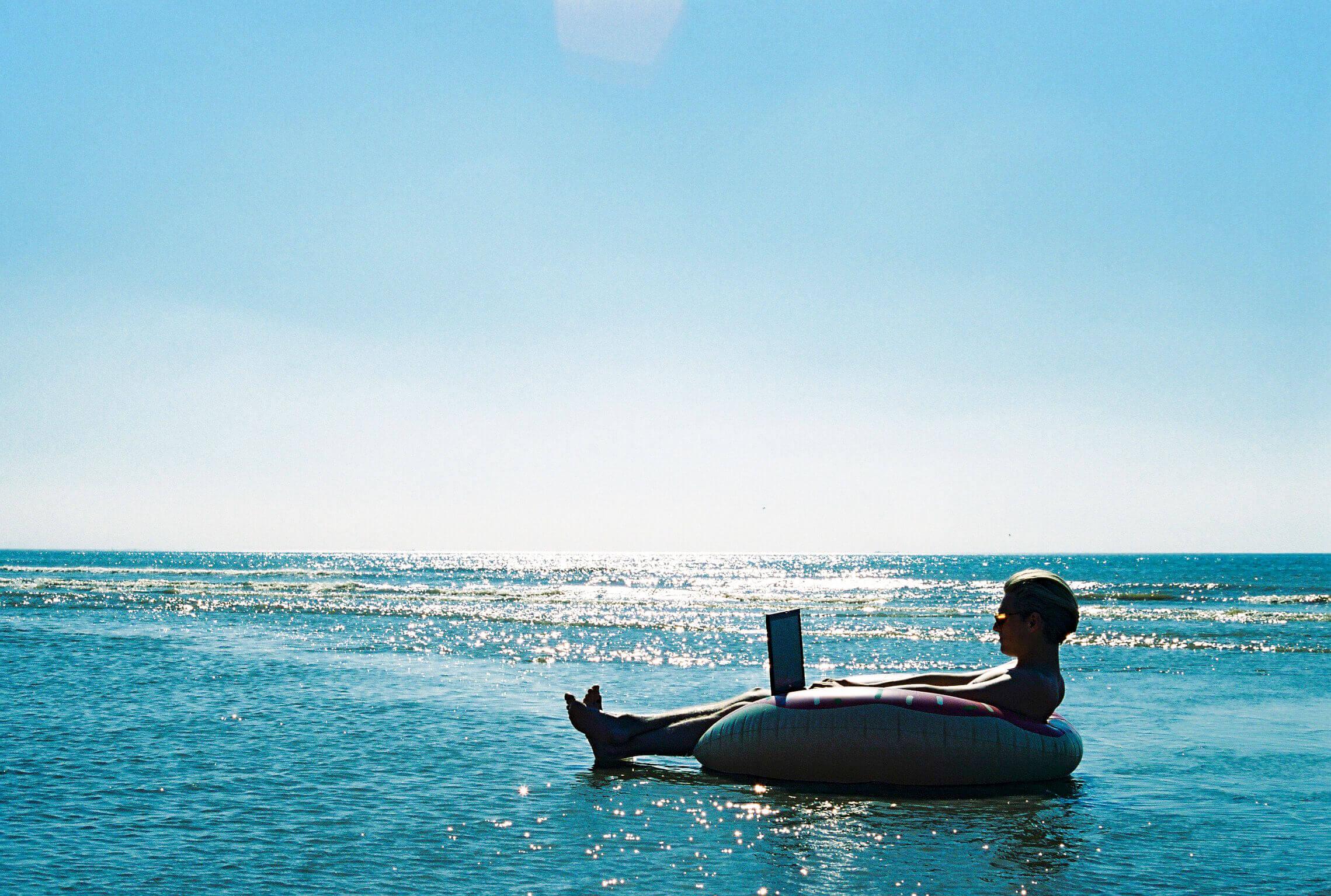 Mann arbeitet in einem Schwimmring auf dem Meer mit einem Laptop