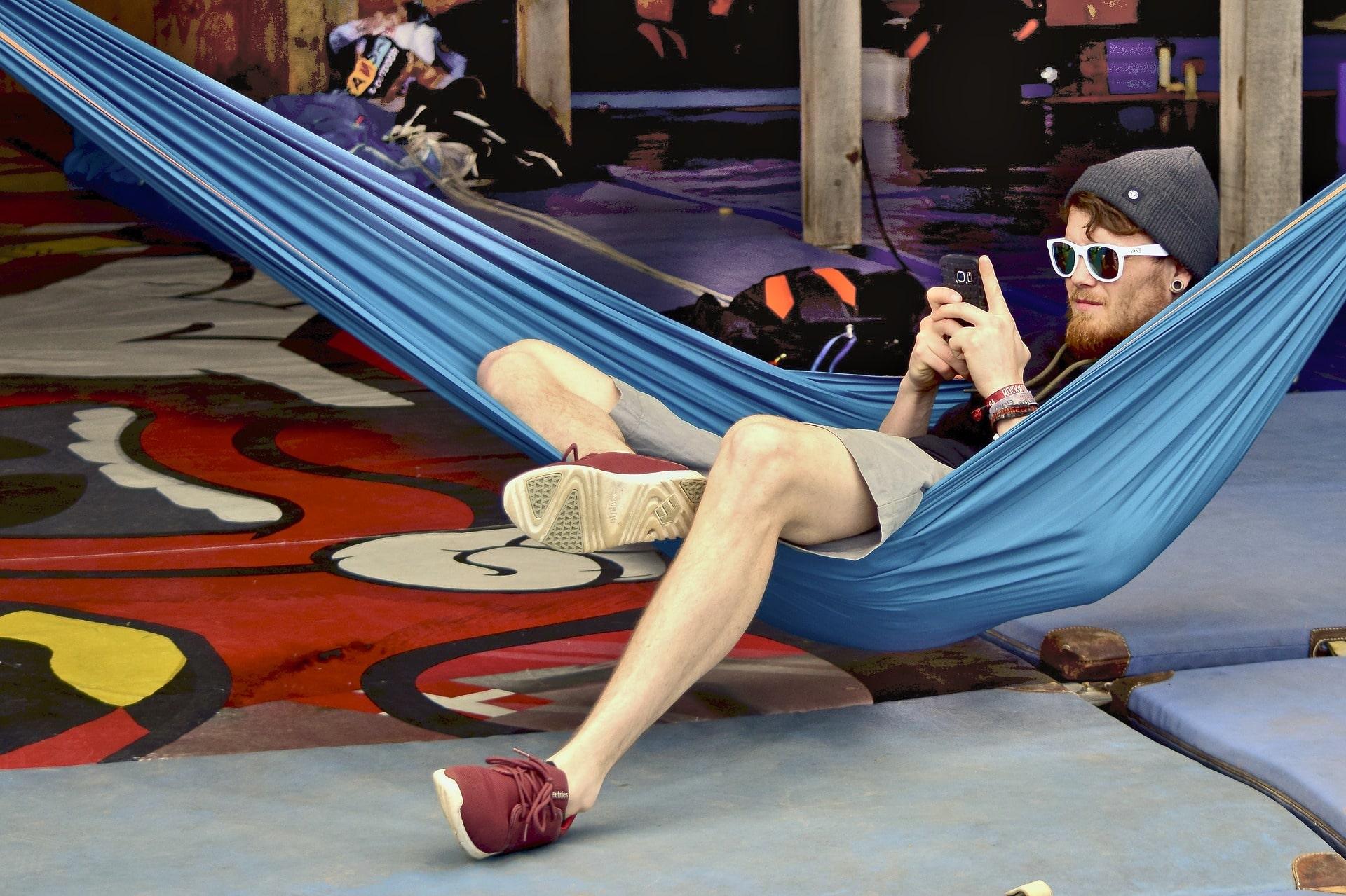 Junger Mann mit Sonnenbrille und Mütze guckt auf sein Handy und sitzt in einer Hängematte